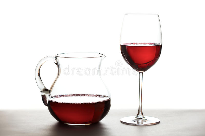 Wine carafe. Red wine in a wine carafe and a wine glass over white background royalty free stock photo