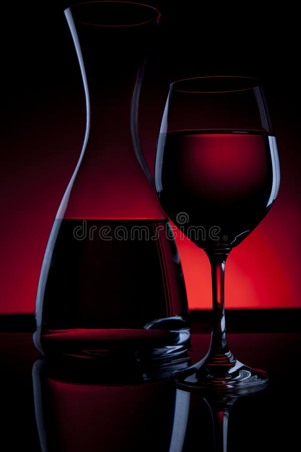 Wine Carafe and Glass on Red stock photos