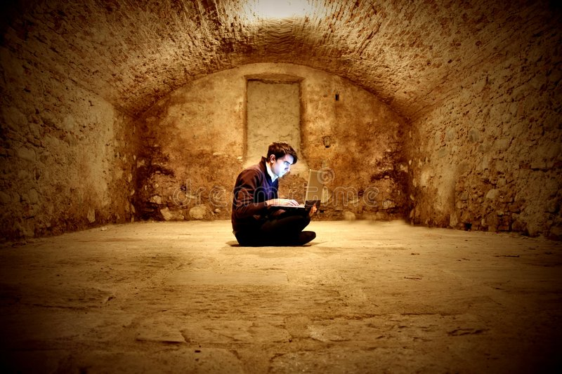 Wine cellar. A young man in a old wine cellar with a laptop