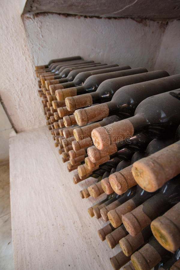 Wine cellar, a row of bottles. Many bottles - lie one above the other, in a niche in the cellar. Bottle with a wooden stopper and covered with dust. Excerpt stock photography