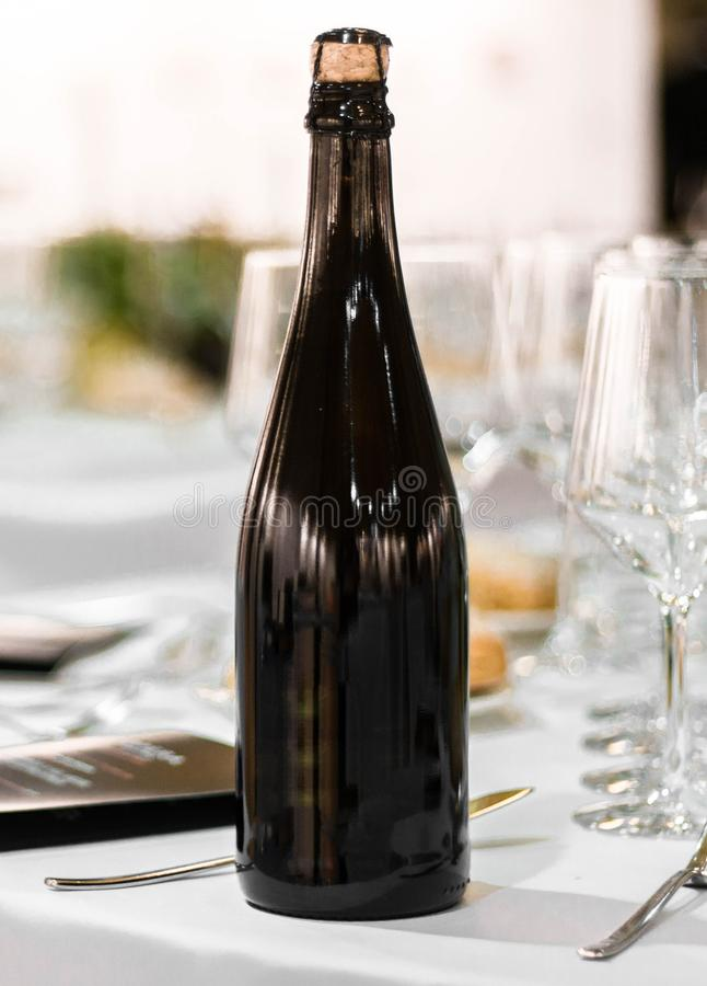 Wine champagne cider dark glass bottle blanck space in fancy table set in restaurant event celebration royalty free stock image