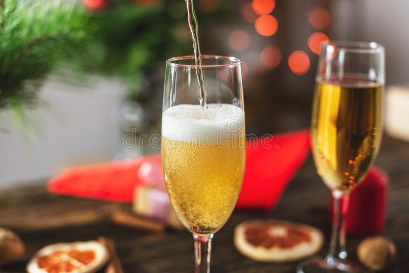 Wine champagne pours into a glass on the background of bokeh garlands. Festive Christmas table on new year`s eve stock photo