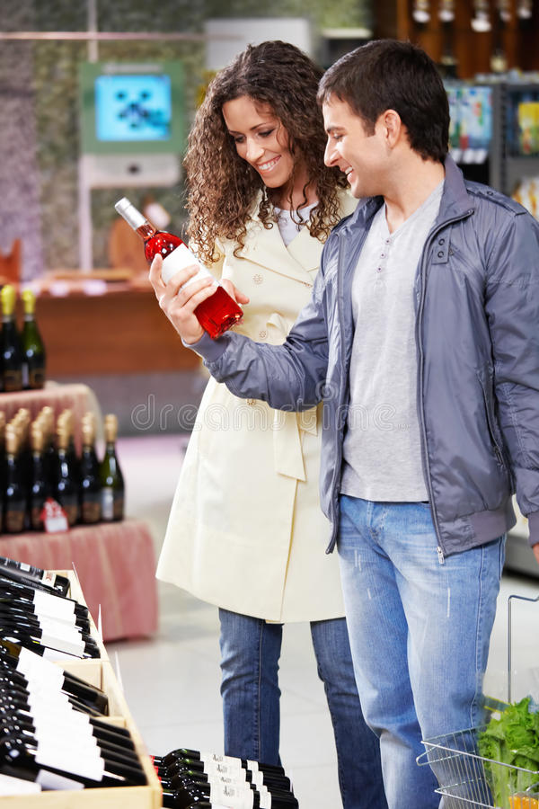 At a wine choice. The young couple chooses wine in shop