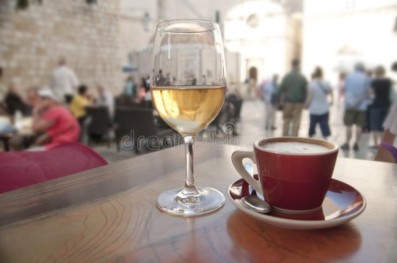 Wine and coffee at a cafe, crowded street background. Wine and coffee at a cafe by a crowded street. Sightseeing concept royalty free stock images