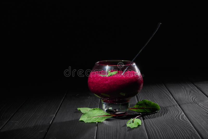 A wine-colored beet smoothie dessert. A big transparent glass filled with thick vegetable cocktail on a black background stock photos