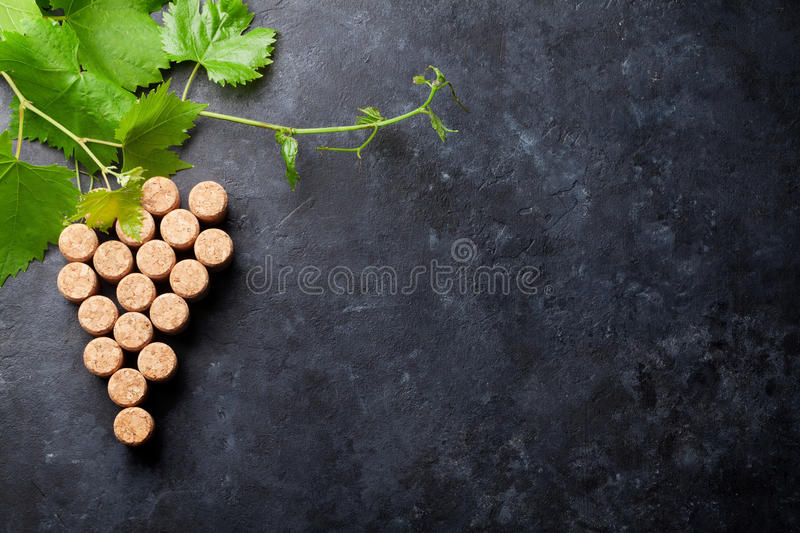 Wine corks grape shape and vine. On stone table. Top view with copy space for your text