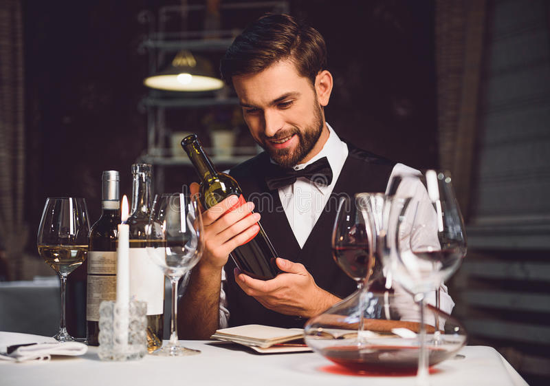 Wine critic holding bottle of scarlet drink with smile stock photography