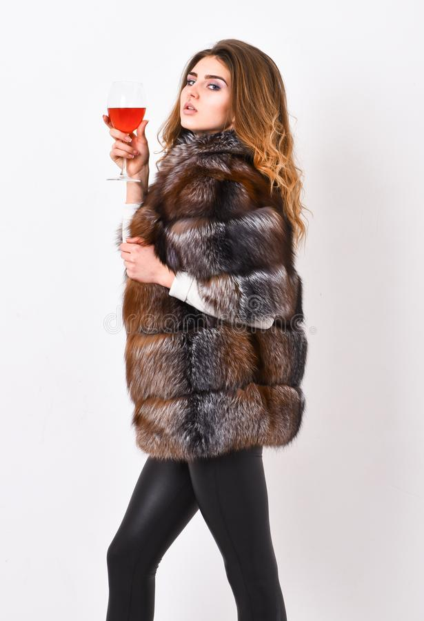 Wine culture concept. Woman drink wine. Girl fashion makeup wear fur coat hold glass alcohol. Elite leisure. Reasons. Drink red wine in wintertime. Lady fashion stock image