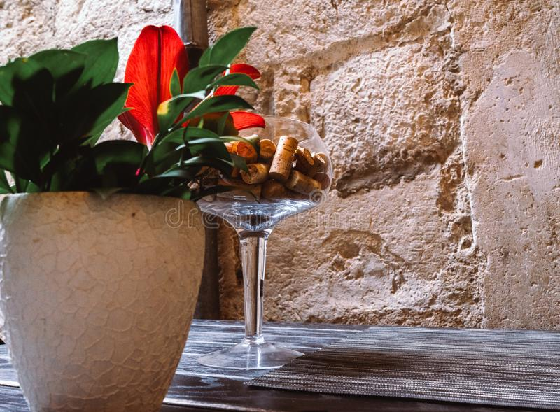Wine cup with corks and vase with flowers in a table in a restaurant. Original decoration in a black table royalty free stock images