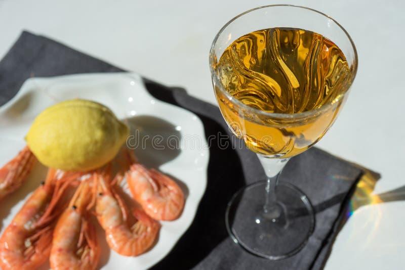 Wine dans un verre sur le fond des fruits de mer à la lumière du soleil lumineuse image libre de droits