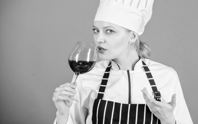 Wine degustation. Which wine to serve with dinner. How to pair wine and food like expert. Girl wear hat and apron enjoy. Aroma of drink. Woman professional chef royalty free stock images