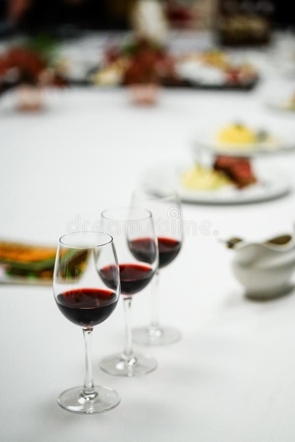 Wine for dinner. Glasses with red wine on dinner table royalty free stock photo