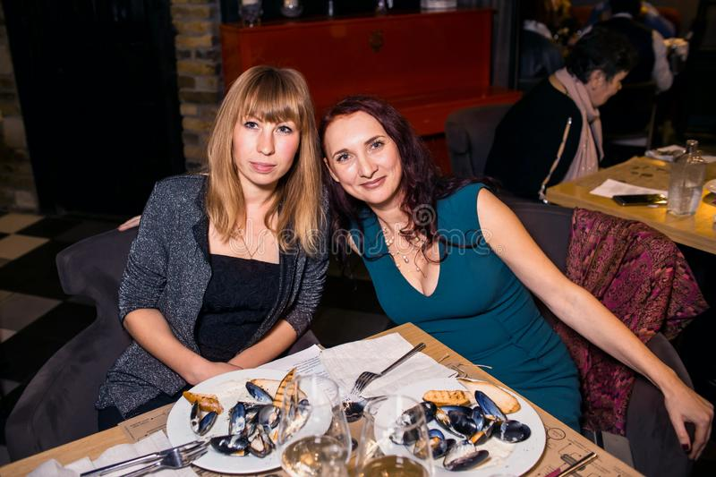 Wine dinner at the restaurant with oysters and seafood. People eat Oysters and risotto gourmet cuisine. Mussels for dinner,. Visitors first try oysters. Russia royalty free stock photo