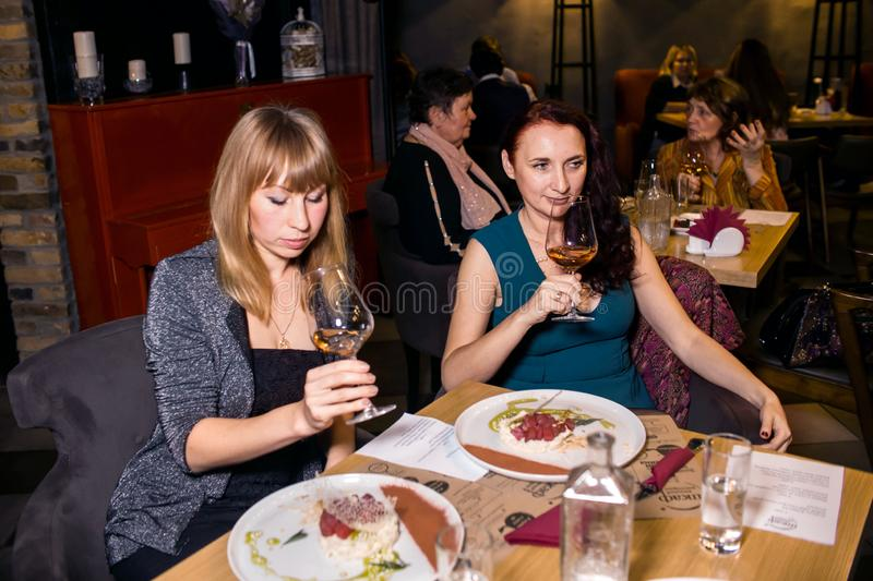 Wine dinner at the restaurant with oysters and seafood. People eat Oysters and risotto gourmet cuisine. Mussels for dinner,. Visitors first try oysters. Russia royalty free stock image