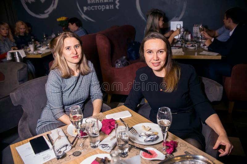 Wine dinner at the restaurant with oysters and seafood. People eat Oysters and risotto gourmet cuisine. Mussels for dinner,. Visitors first try oysters. Russia stock photo