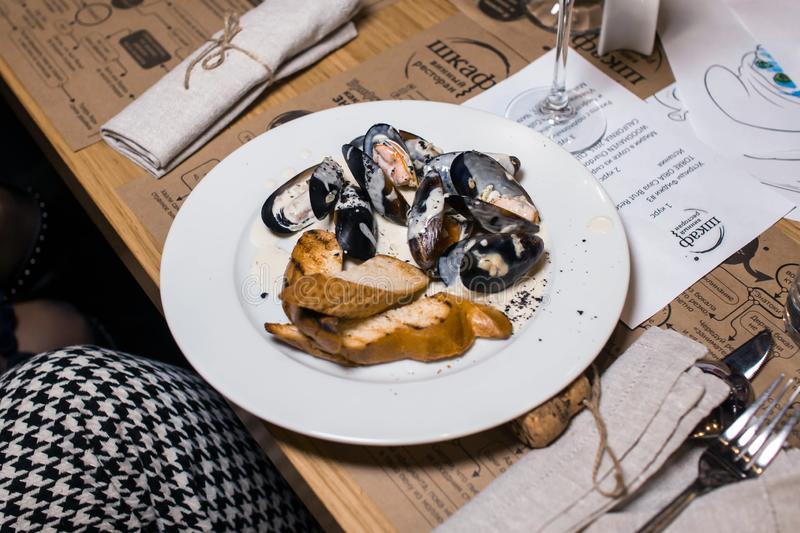 Wine dinner at the restaurant with oysters and seafood. Oysters and risotto gourmet cuisine. Mussels for dinner. Russia,. Sverdlovsk, 19 October 2018 stock photography
