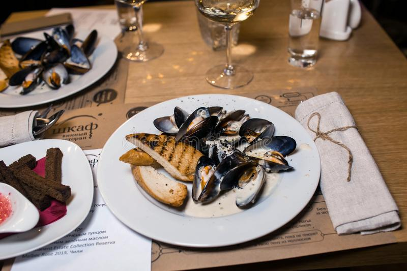 Wine dinner at the restaurant with oysters and seafood. Oysters and risotto gourmet cuisine. Mussels for dinner. Russia,. Sverdlovsk, 19 October 2018 royalty free stock photography