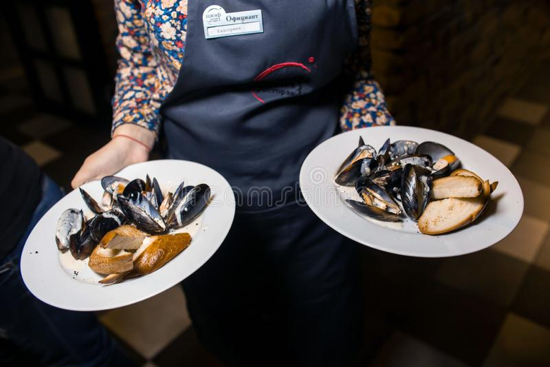 Wine dinner at the restaurant with oysters and seafood. Oysters and risotto gourmet cuisine. Mussels for dinner. Russia,. Sverdlovsk, 19 October 2018 royalty free stock photo