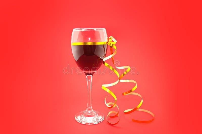 Wine en verres avec le ruban d'or sur le fond rouge images libres de droits