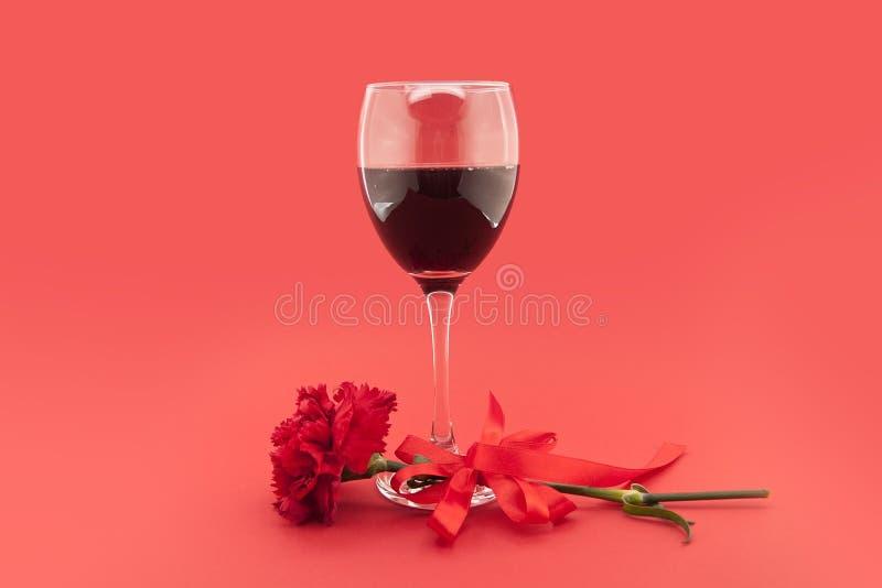 Wine en verres, oeillet rouge avec le ruban blanc sur le rouge photographie stock