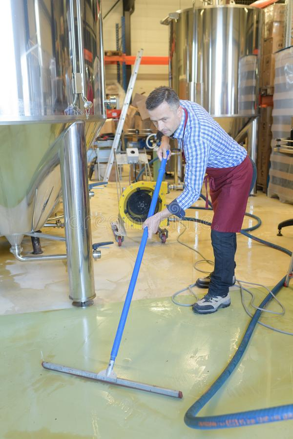 Wine factory worker cleaning floor. Man royalty free stock images