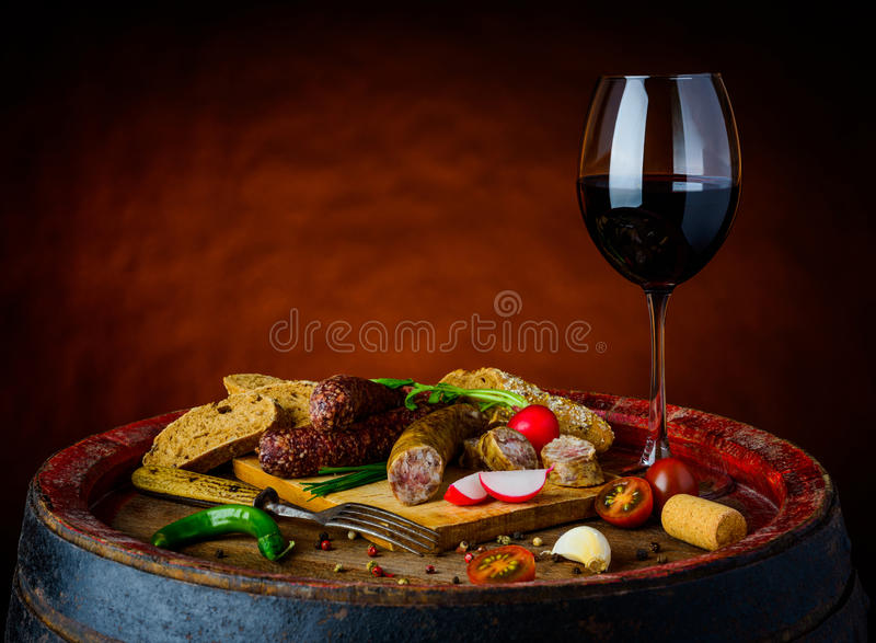 Wine and food. Rustic food and one glass of red wine on wooden rustic barrel in still life royalty free stock image