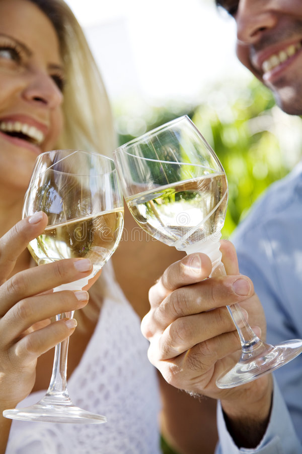 Wine in the garden. Young couple enjoying a glass of white wine in the garden