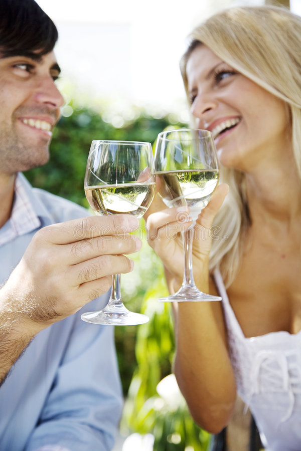 Wine in the garden. Young couple enjoying a glass of white wine in the garden on a summer day