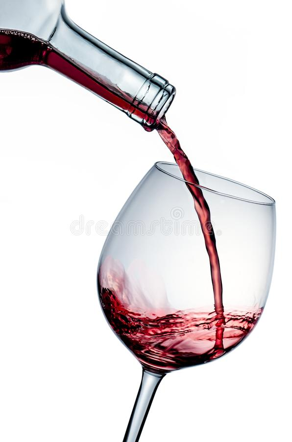 Wine in the glass. Bottle pouring wine into a glass royalty free stock photography