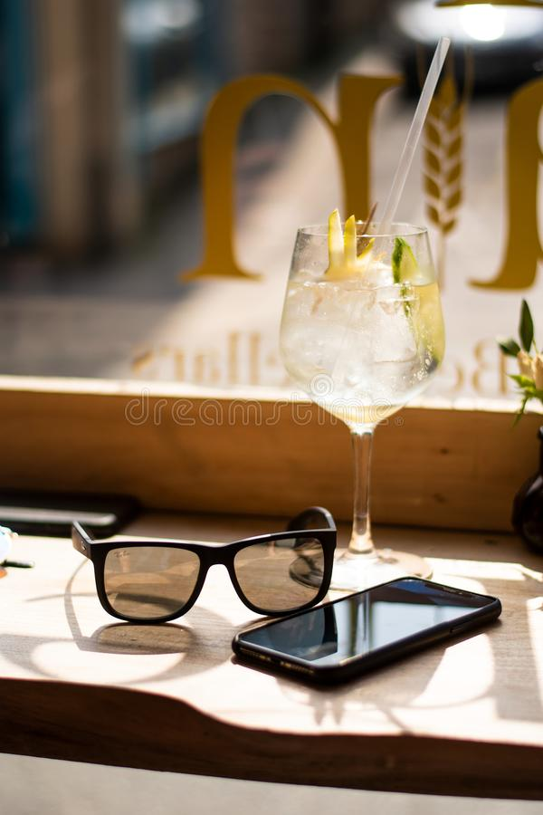 Wine Glass Beside Android Smartphone and Sunglasses royalty free stock images