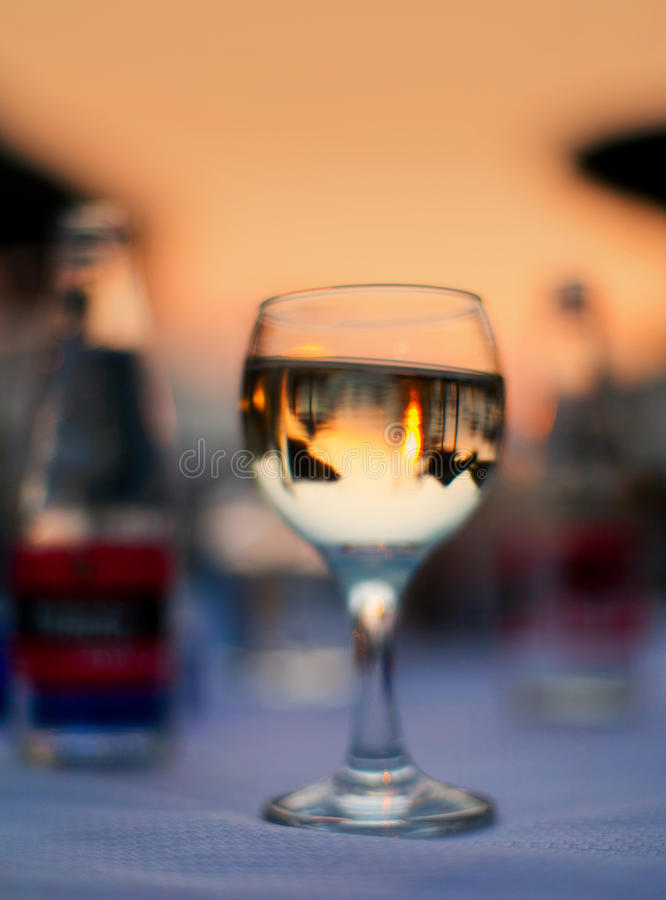 Wine glass on beach table. At sunset in Greece, sun and umbrellas reflected royalty free stock photography