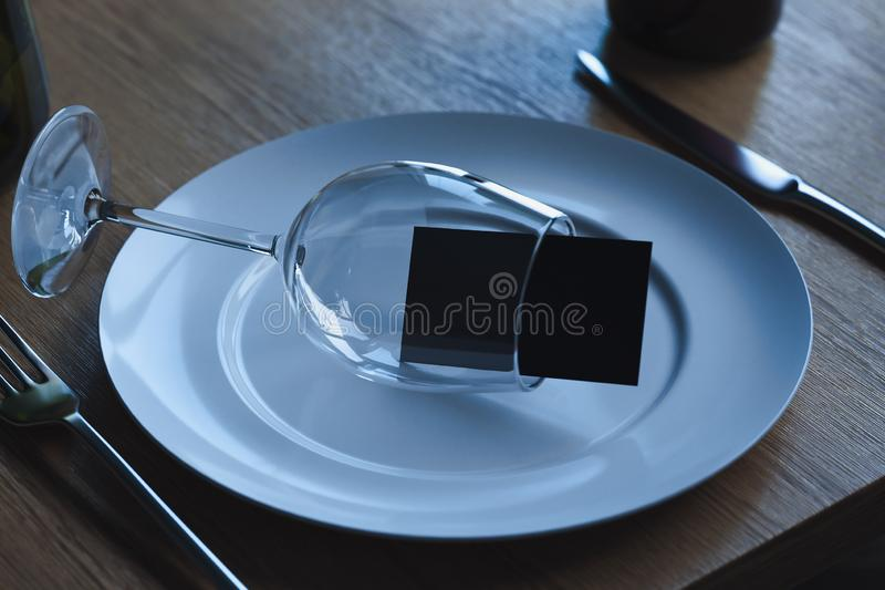 Wine glass with blank business card inside on white dish plate. 3d rendering. stock illustration