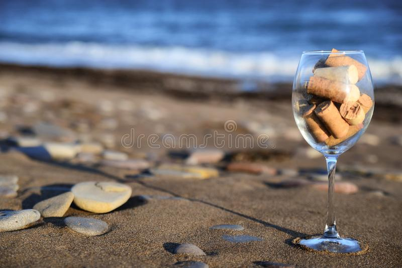 Wine glass with cork stoppers on the beach. Large wine glass filled with cork stoppers stands on a sandy beach against the sea royalty free stock photography