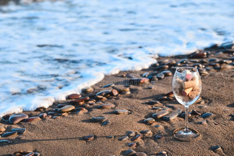 Wine glass with cork stoppers on the beach. Large wine glass filled with cork stoppers stands on a sandy beach against the sea royalty free stock photos