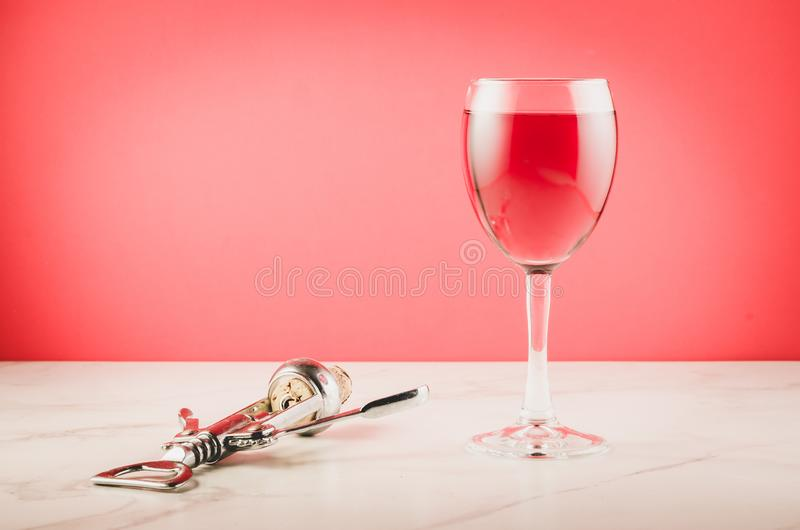 Wine glass and corkscrew on pink background/Wine glass and corkscrew on pink  background. Selective focus and copyspace royalty free stock photography