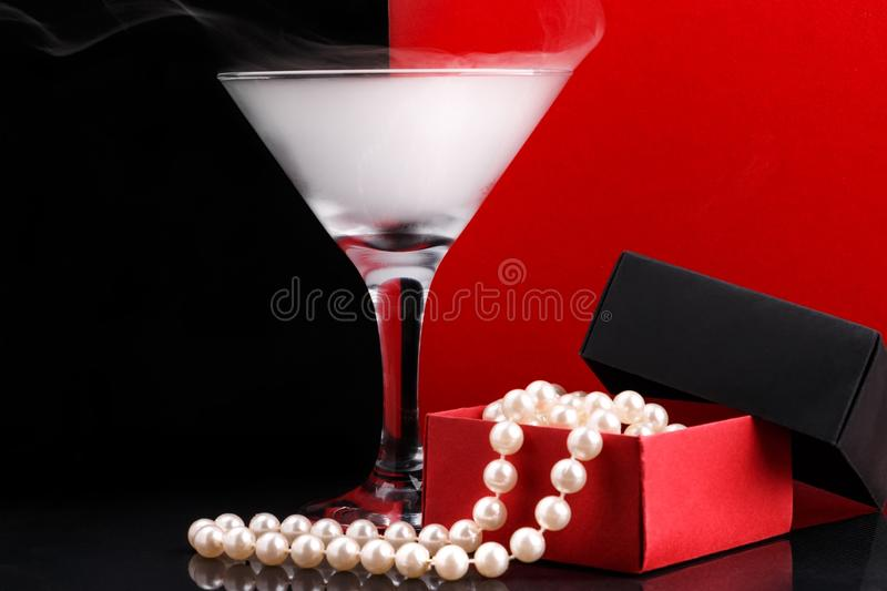 Wine glass with fog and perl beads in opened paper giftbox on black and red background. Wine glass with white fog and perl beads in opened homemade paper giftbox stock image