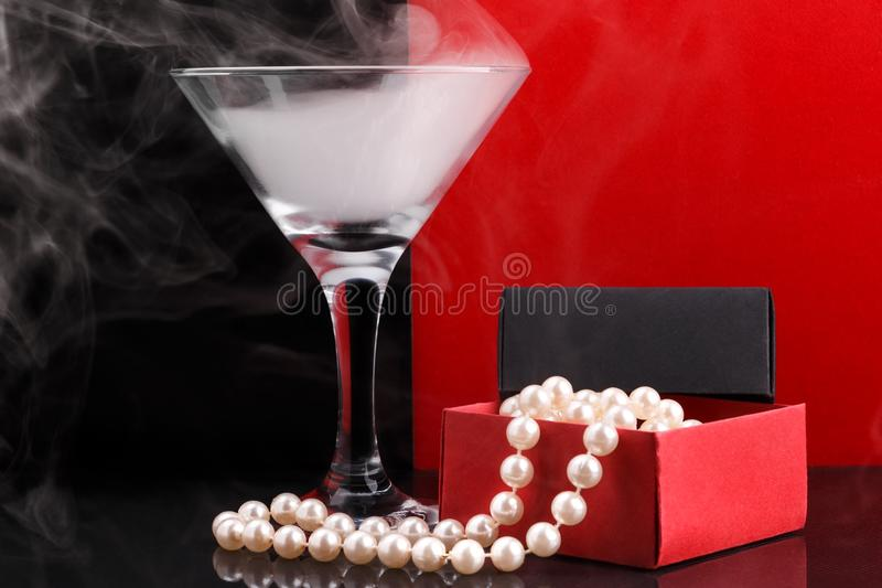 Wine glass with fog and perl beads in opened paper giftbox on black and red background. Wine glass with white fog and perl beads in opened homemade paper giftbox stock photo