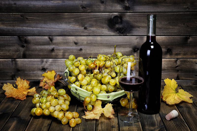 Wine glass and fresh bunch of white grapes on antique wooden background. stock photo