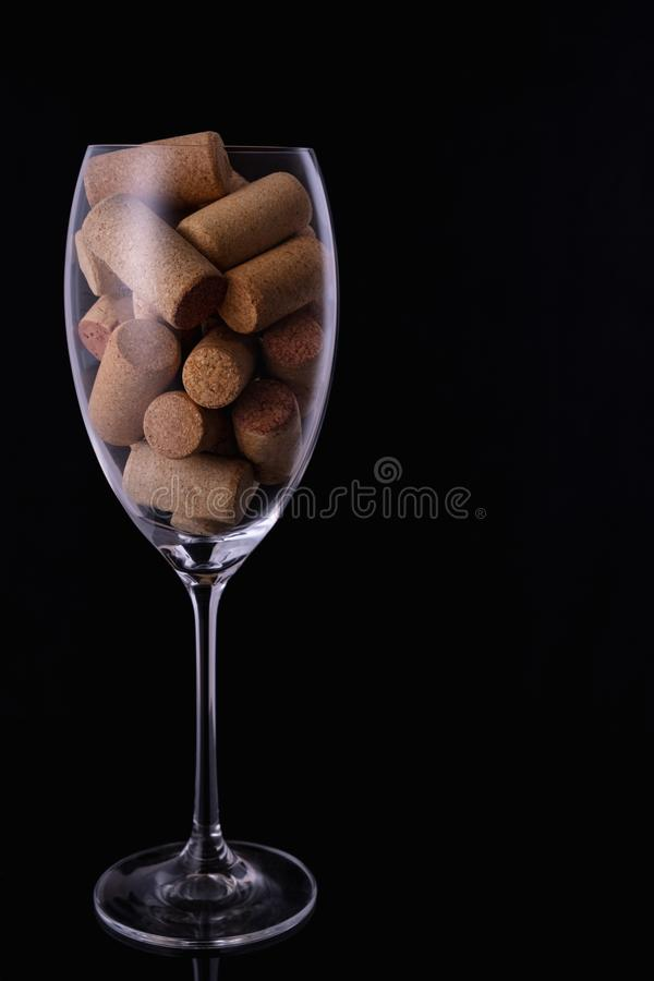 Wine glass full of wine cork stoppers on black  background and copy space. Wine glass full of wine cork stoppers on black background and copy space stock photo