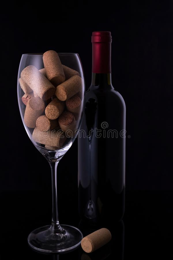 Wine glass full of wine cork stoppers wine bottle on black background and  copy space. Wine glass full of wine cork stoppers wine bottle on black background and stock photography