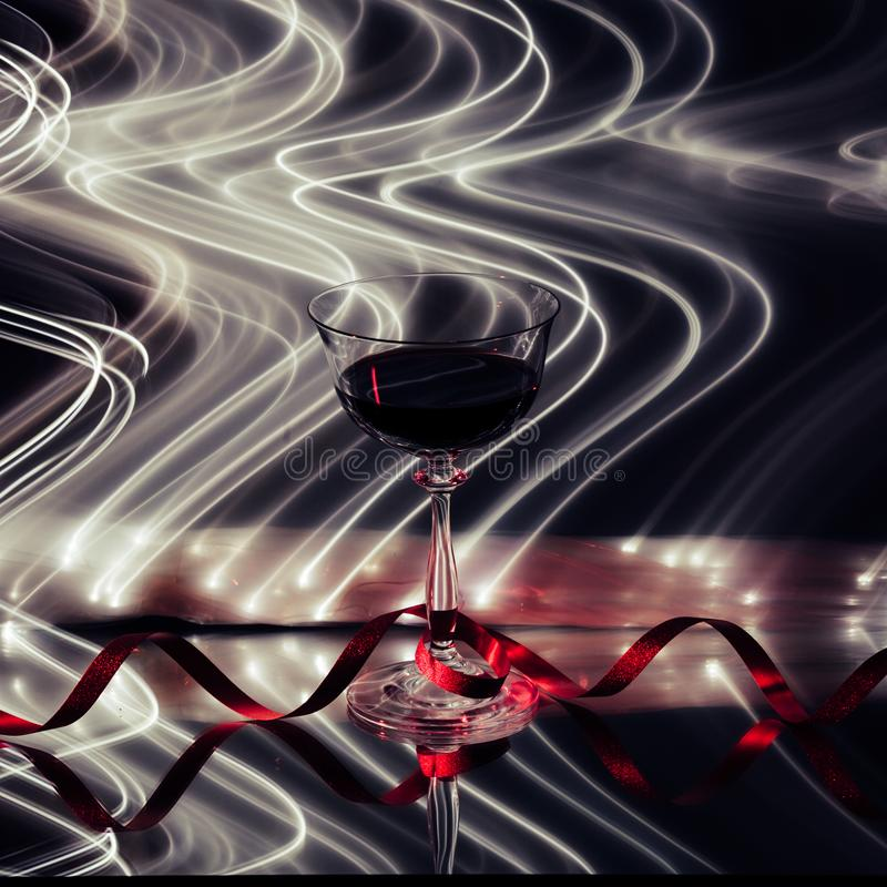 Wine glass, with lines of lights in the background stock photo