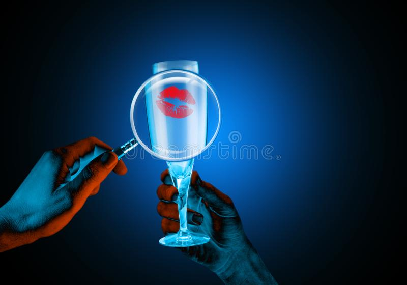 Wine glass with a lipstick mark magnified by a magnifying glass. Creative blacklight lighting stock photography