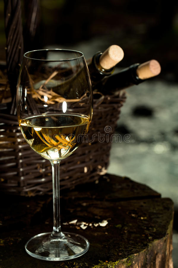 Wine glass near bottles in basket. Wine glass and bottles in picnic basket with straw on stump. Vintage look stock photos