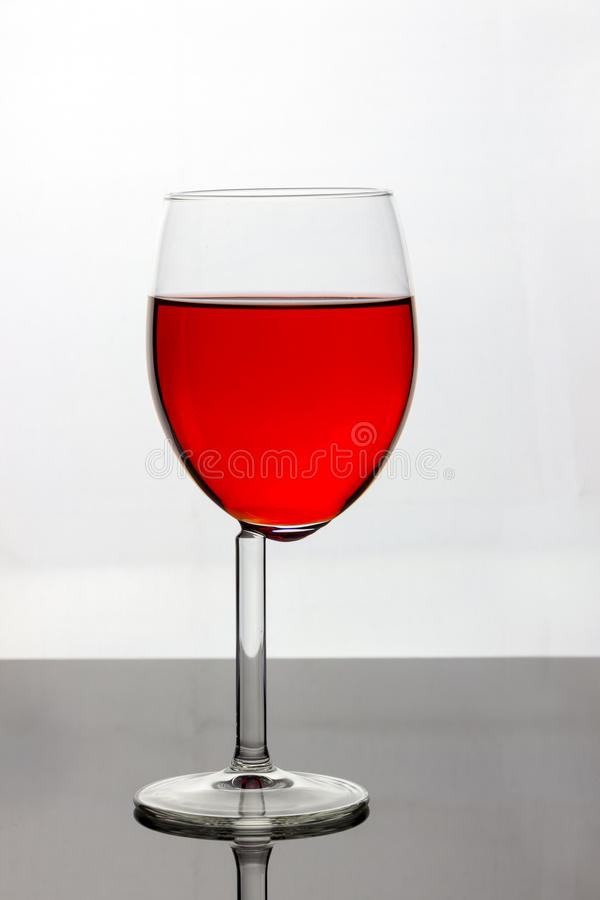 Wine glass with red liquid. An odd wine glass with red liquid/wine on a white background stock photography