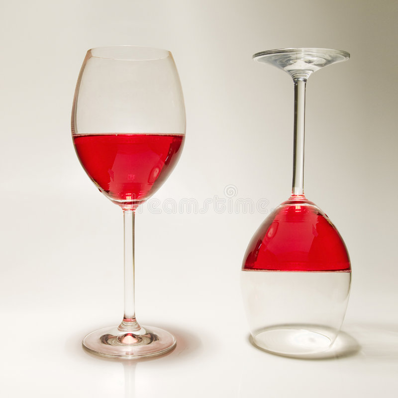 Wine glasses. Two paradoxical wine glasses filled with red wine royalty free stock photography