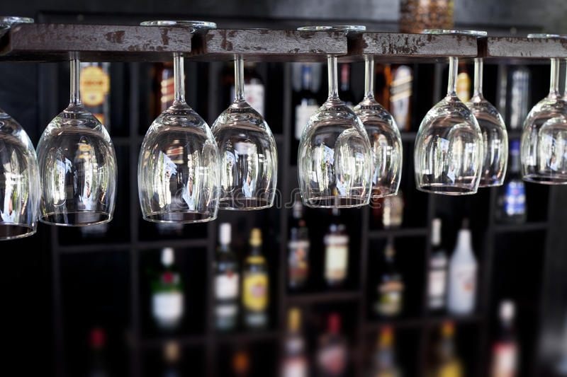 Wine glasses in a bar. Wine glasses hanging upside down in a bar with bottles blurred in the background stock photography