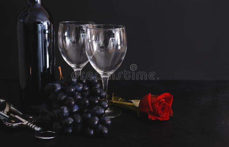 2 wine glasses, a bottle of red wine, a bunch of dark grapes, a metal corkscrew, a red rose on a black background stock images