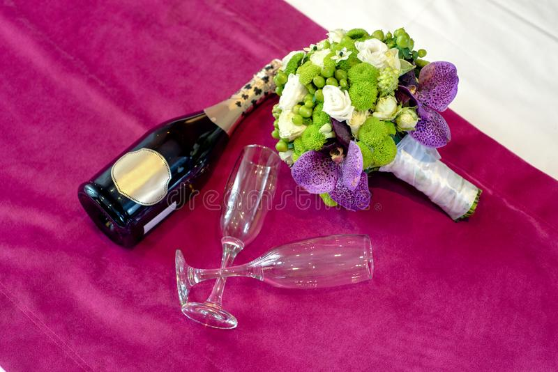 Bouqet and wine. Wine, glasses and bride`s bouqet on bed stock image