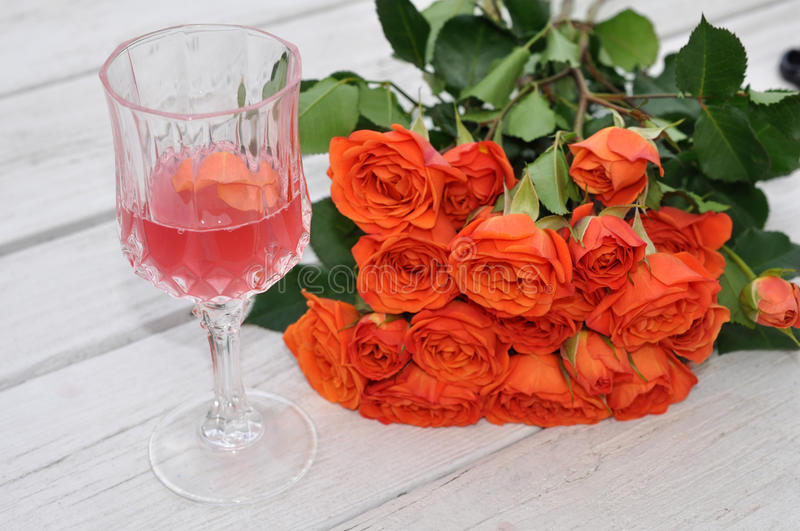 Wine glasses and bunches of rose stock images