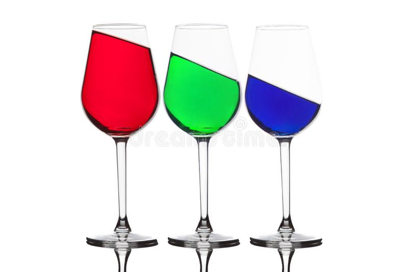 WIne glasses with different coloured drinks. Three different colored wine glasses isolated on white. Red, green and blue - RGB royalty free stock photos